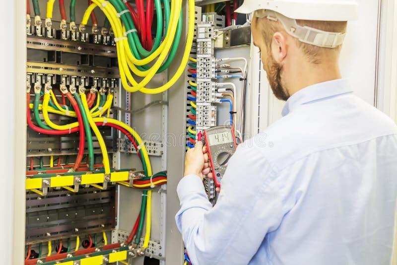 O coordenador do eletricista no capacete branco testa o painel da tensão do poder do circuito trifásico Coordenador bonde com mul foto de stock royalty free