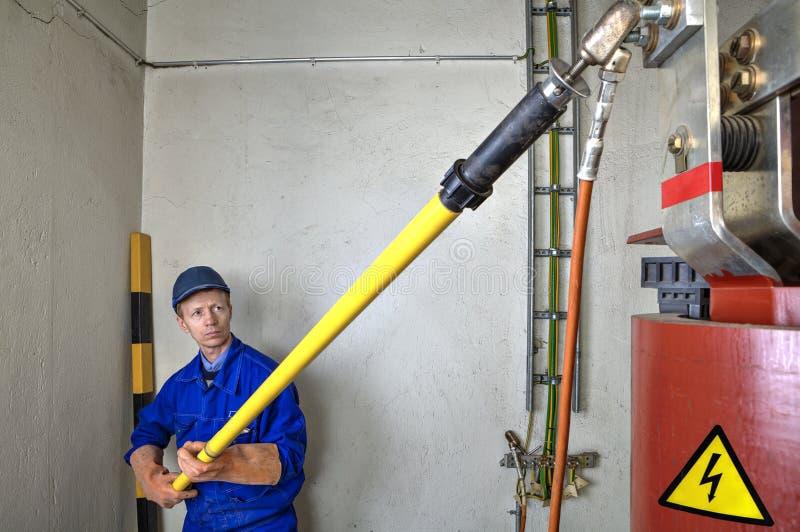 O coordenador do eletricista usa a vara de isolamento à terra que aterra o tr fotografia de stock royalty free