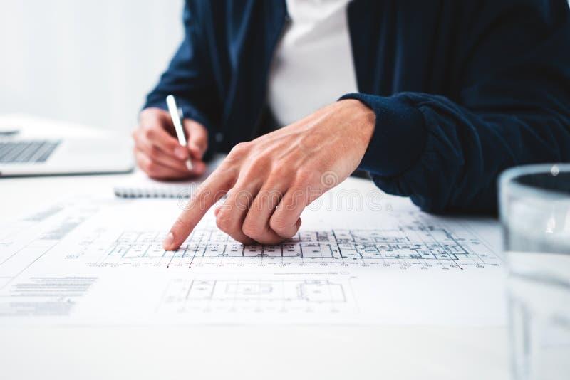 O coordenador do homem que olha o quando do desenho e do computador senta-se pela tabela no escritório do sótão fotos de stock royalty free