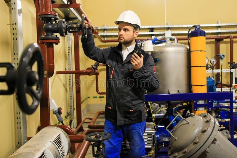 O coordenador do técnico abre a válvula de porta do encanamento na refinaria de petróleo imagem de stock