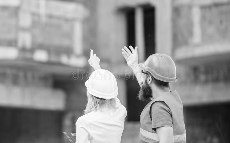 O coordenador e o construtor da mulher comunicam o canteiro de obras Relacionamentos entre clientes da constru??o e participante fotos de stock