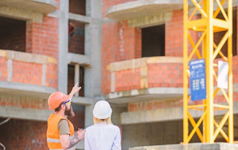 O coordenador e o construtor da mulher comunicam-se no canteiro de obras Relacionamentos entre clientes da constru??o e participa fotografia de stock royalty free