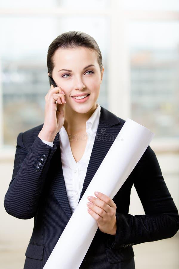 O coordenador fêmea com disposição fala no telefone imagem de stock royalty free