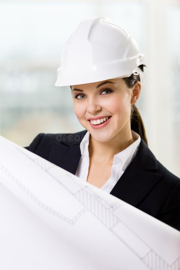 O coordenador fêmea no capacete de segurança entrega o esboço fotografia de stock royalty free