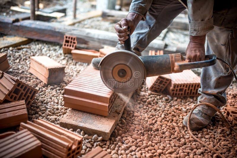 O coordenador industrial que trabalha em tijolos do corte no canteiro de obras, usando um moedor, mitra elétrica viu com lâmina a fotos de stock