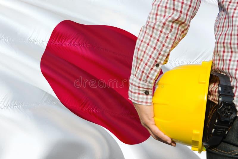 O coordenador japonês está guardando o capacete de segurança amarelo com ondulação do fundo da bandeira de Japão Conceito da cons fotografia de stock