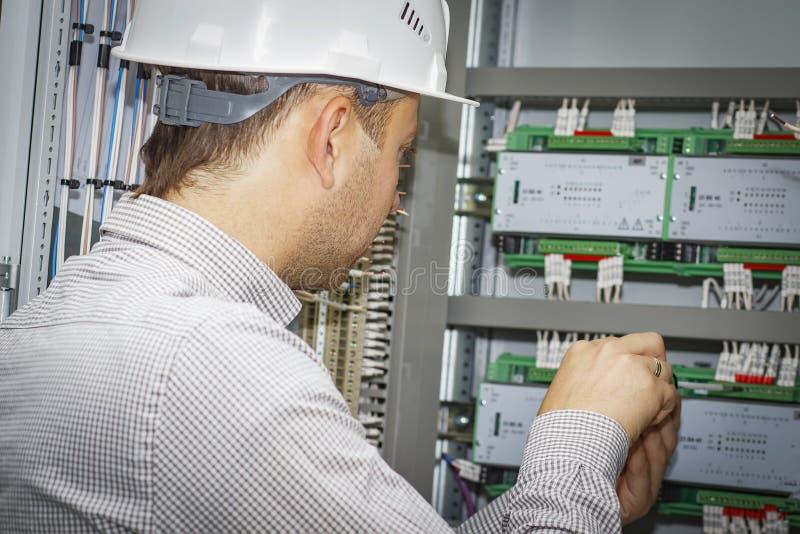O coordenador monta o controlador para a automatização de processo no armário de controle O eletricista no capacete branco ajusta fotos de stock