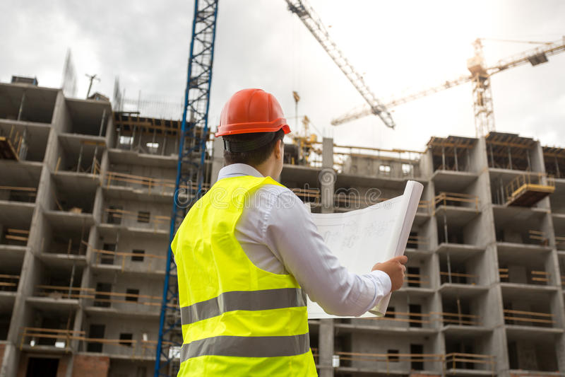 O coordenador no terreno de construção examina modelos fotos de stock royalty free