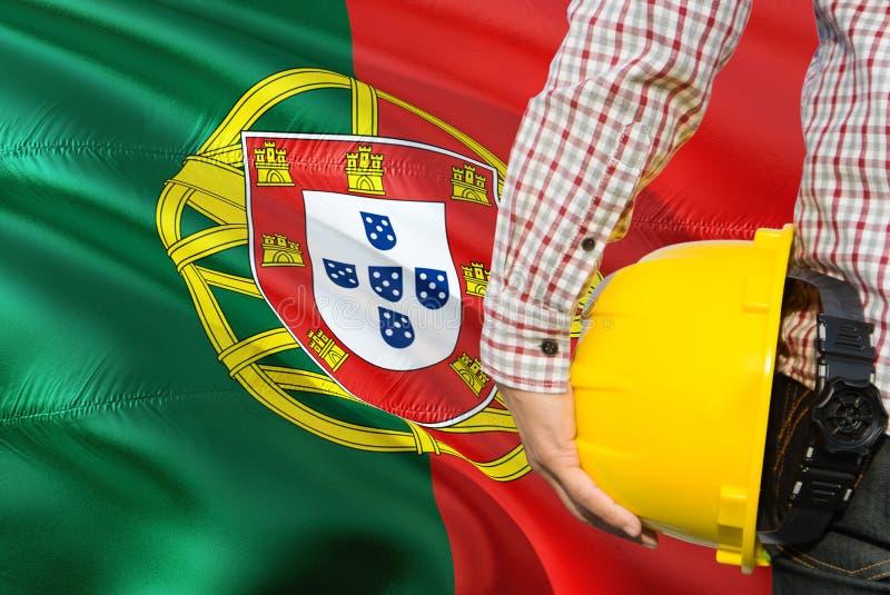 O coordenador português está guardando o capacete de segurança amarelo com ondulação do fundo da bandeira de Portugal Conceito da imagem de stock royalty free