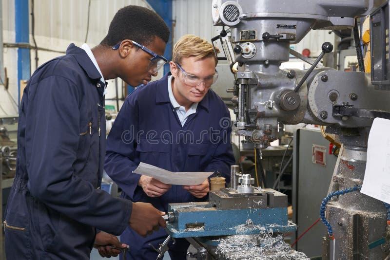 O coordenador Showing Apprentice How a usar-se fura dentro a fábrica imagem de stock
