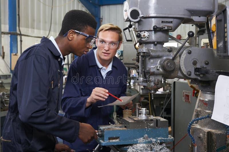 O coordenador Showing Apprentice How a usar-se fura dentro a fábrica fotos de stock royalty free
