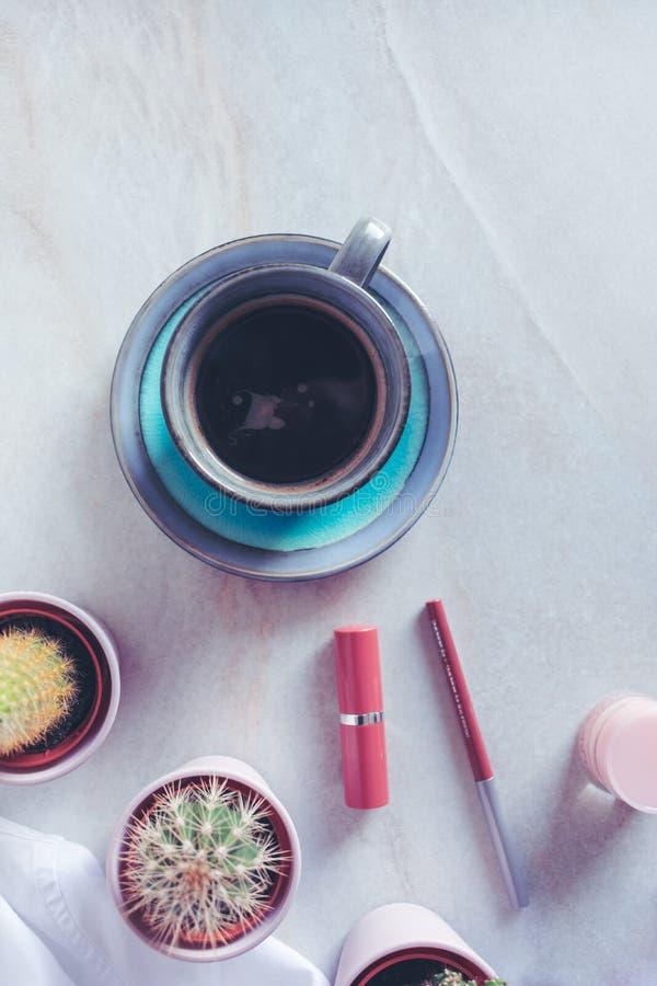 O copo azul do café preto, compõe e cactos ou plantas carnudas no fundo de mármore foto de stock