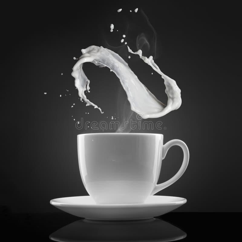 O copo branco com líquido quente e o leite espirram no preto imagens de stock royalty free