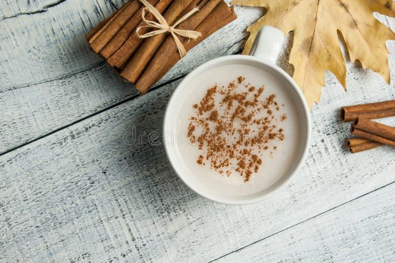 O copo branco da bebida quente leitosa do salep de Turquia com pó da canela e as varas inverno saudável da especiaria e do outono imagens de stock royalty free