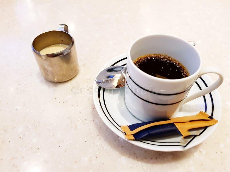 O copo branco do café quente do café com saco do açúcar mascavado, a colher pequena e a caneca do leite na tabela de mármore com  foto de stock