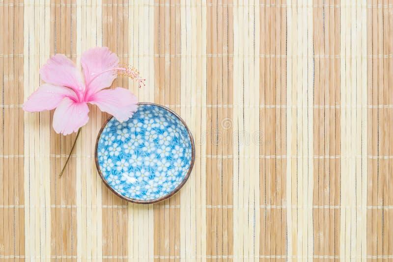 O copo cerâmico bonito do close up para a sopa com a flor cor-de-rosa na esteira de madeira borrada textured o fundo imagens de stock
