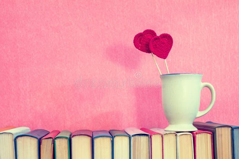 O copo com vermelho faz crochê corações em livros imagens de stock