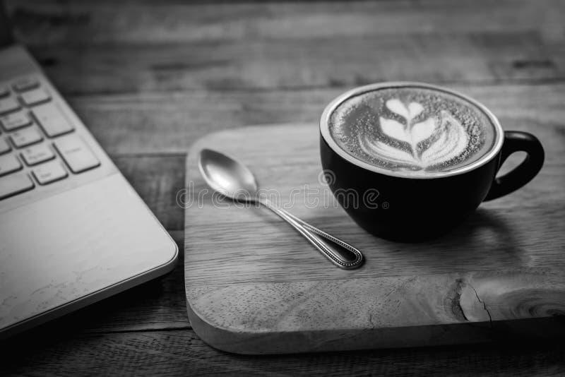 O copo de café quente da arte do latte na tabela, o vintage e o estilo retro enegrecem fotografia de stock