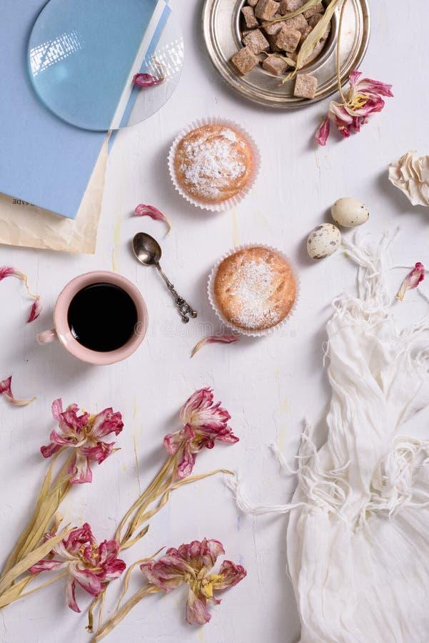 O copo de café, queques com tulipa cor-de-rosa floresce na tabela rústica branca de cima de, no café da manhã no dia de mães ou n fotos de stock