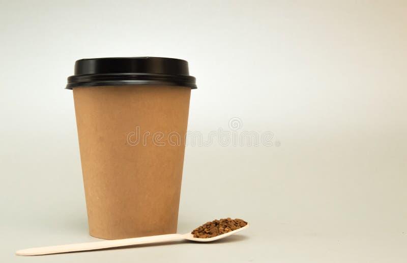 O copo de papel para o caf? com uma tampa preta em um fundo claro, ao lado dele ? uma colher de madeira com caf? imagens de stock royalty free
