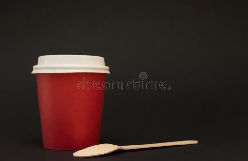 O copo de papel vermelho com uma tampa para suportes do café em um fundo preto, ao lado dele é uma colher de café de madeira imagens de stock royalty free