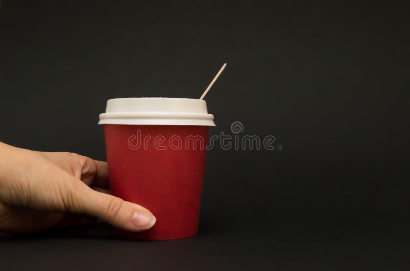 O copo de papel vermelho para o café com uma tampa em um fundo preto, mão está guardando um copo de papel imagens de stock