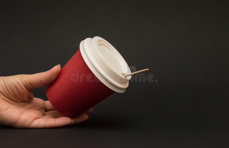 O copo de papel vermelho para o caf? com uma tampa em um fundo preto, m?o est? guardando um copo de papel imagem de stock