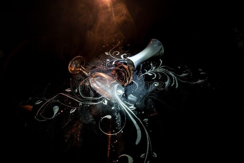 O copo de vinho quebrado e murchado aumentou no fundo escuro Uma rosa murchando significa amor perdido, divórcio, ou um relaciona foto de stock royalty free