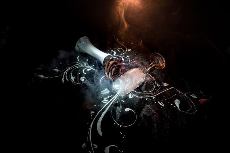 O copo de vinho quebrado e murchado aumentou no fundo escuro Uma rosa murchando significa amor perdido, divórcio, ou um relaciona imagem de stock royalty free