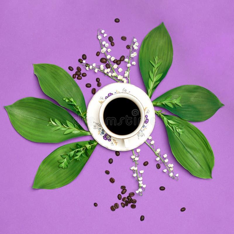 O copo do café preto com as flores no roxo coloriu o fundo da arte Instalação floral do café do bom dia foto de stock
