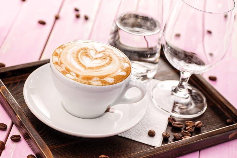 O copo do cappuccino com espuma do coração, grupo de xícara de café com os feijões de café no fundo de madeira cor-de-rosa, bebe  fotos de stock