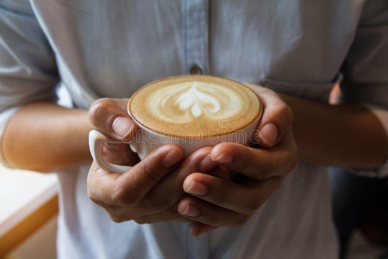 O copo do cappuccino estava guardando pelas mãos da senhora fotos de stock