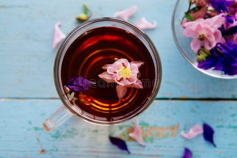 O copo do chá com camomila floresce no fundo de madeira rústico fotografia de stock