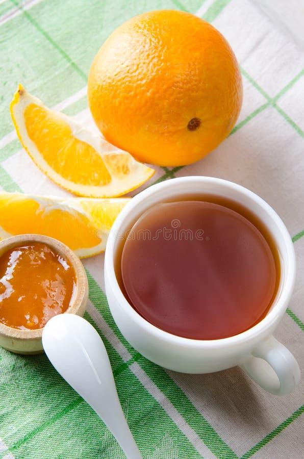 O copo do chá serviu com doce alaranjado fotos de stock royalty free