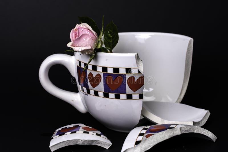 O copo do coração quebrado obteve quebrado com a rosa cor-de-rosa no fundo preto fotografia de stock