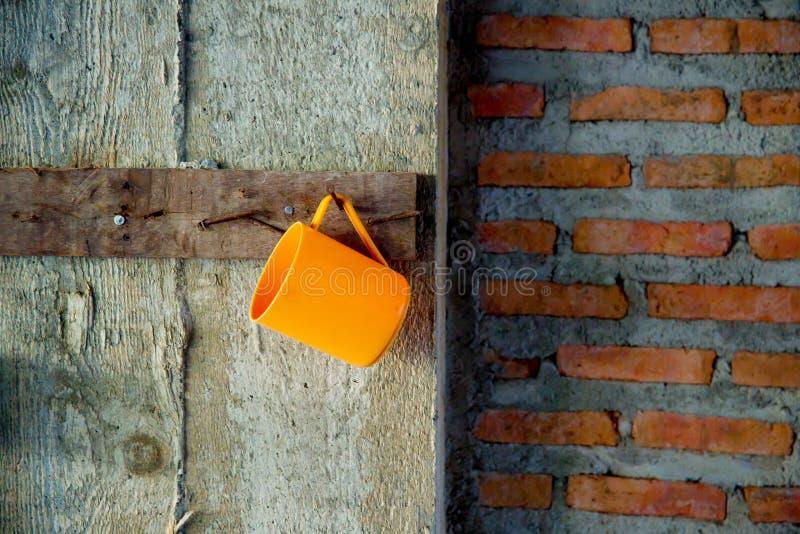 O copo pastic de Orance está pendurando na parede do grunge por um prego imagem para o espaço do bacakground, do papel de parede, fotografia de stock