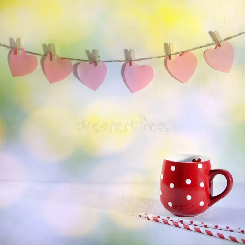 O copo vermelho em um ponto branco está em uma tabela de madeira branca Cair de papel dos corações na parede imagens de stock