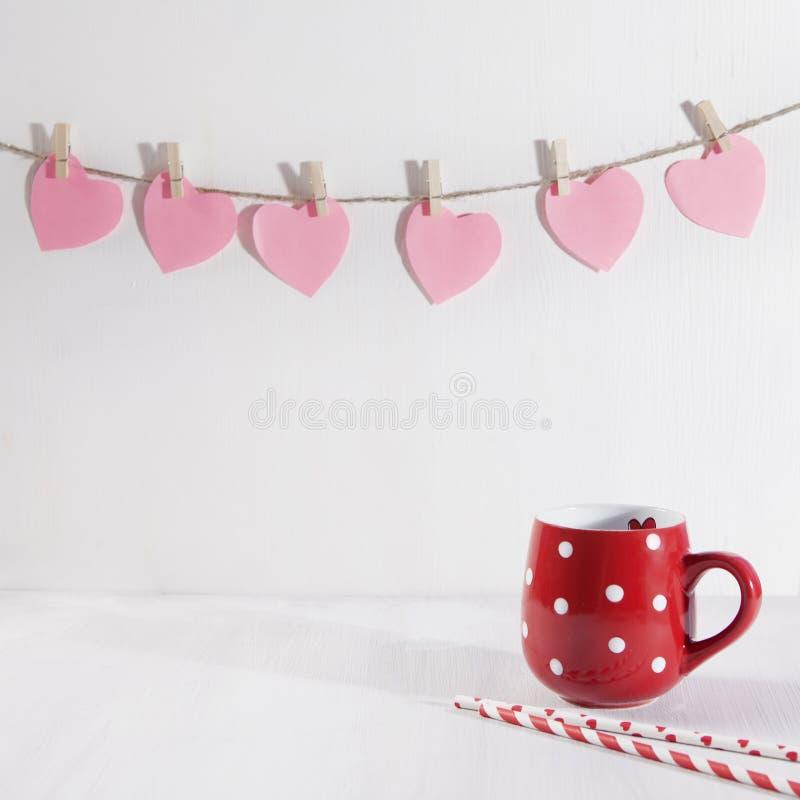 O copo vermelho em um ponto branco está em uma tabela de madeira branca Cair de papel dos corações na parede imagem de stock