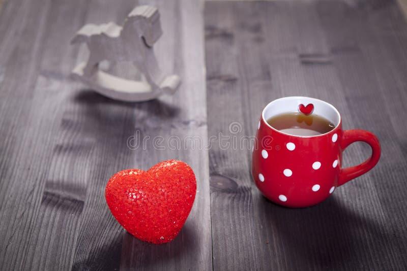 O copo vermelho em um ponto branco está em uma tabela de madeira branca Cair de papel dos corações na parede imagens de stock royalty free