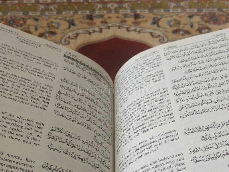 O Corão santamente em inglês e em árabe Oriental-teste padrão bonito em um tapete denominado imagens de stock