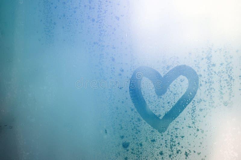 O coração é pintado no vidro misted no inverno imagem de stock