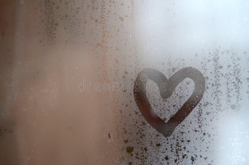 O coração é pintado no vidro misted no inverno foto de stock