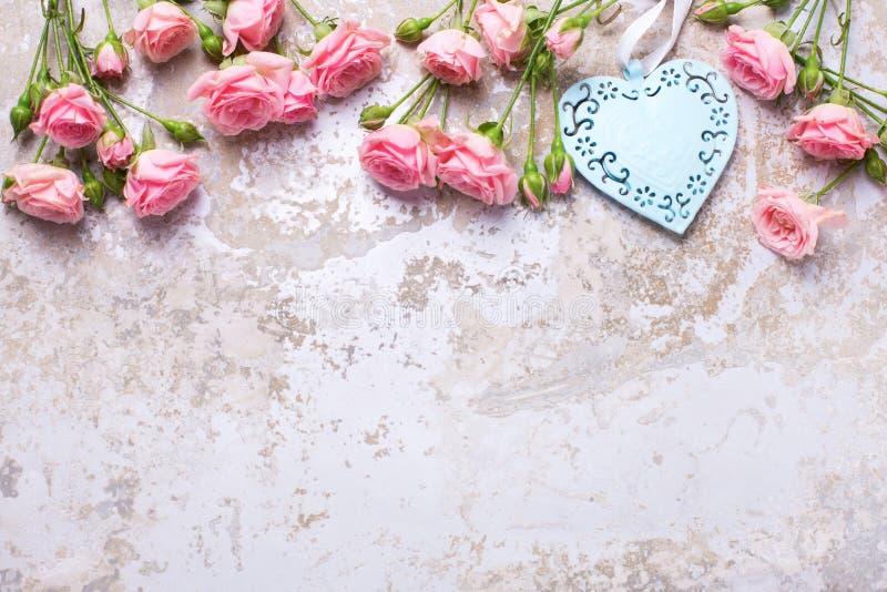 O coração azul e as rosas cor-de-rosa florescem vintage cinzento no backg textured fotos de stock royalty free
