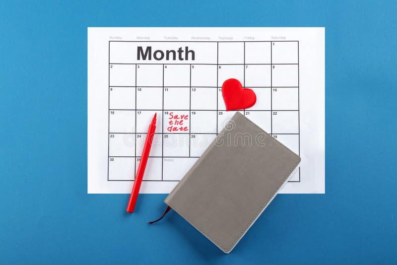 O coração, o caderno e o calendário com inscrição salvar a data no fundo da cor imagem de stock