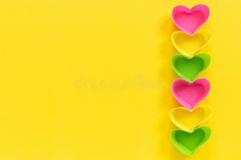 O coração colorido do silicone deu forma ao prato dos moldes para os queques de cozimento alinhados no lado direito da fileira no fotografia de stock royalty free