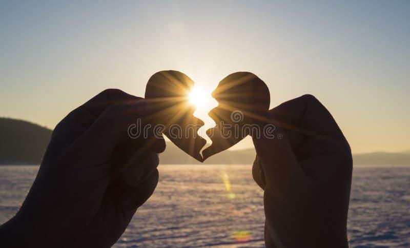O coração conecta as mãos dos amantes, silhueta no por do sol, o dia de todos os amantes imagens de stock