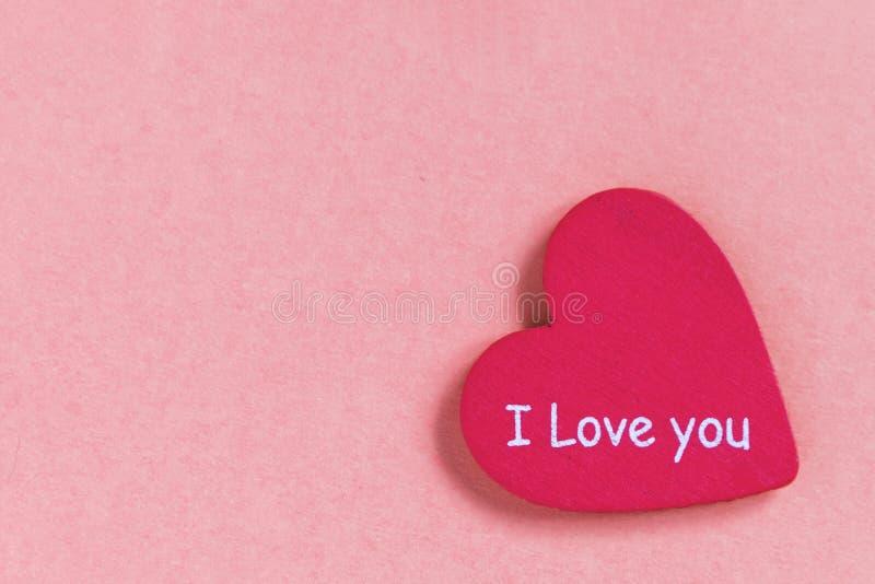O coração cor-de-rosa com texto ama-o no fundo cor-de-rosa foto de stock