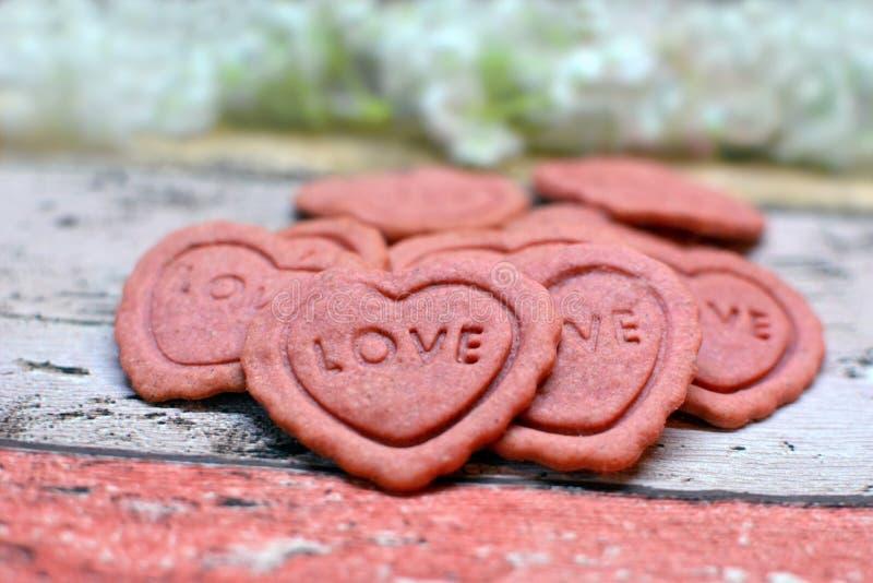 O coração cor-de-rosa deu forma a Valentine Day que em casa cozido as cookies com a palavra amam neles fotos de stock royalty free