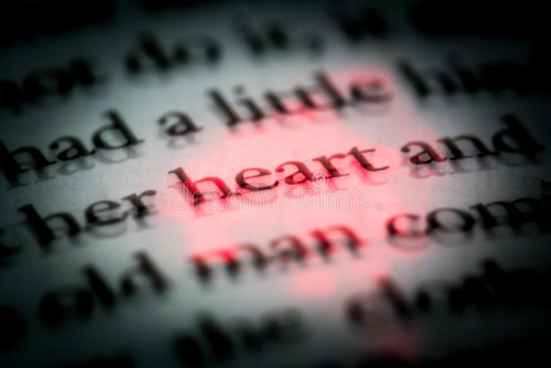O coração da palavra em um livro no fim inglês acima, macro, destacado no vermelho O texto no livro com efeito 3D fotografia de stock royalty free