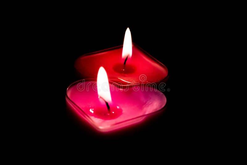 O coração de dois amores deu forma a velas em um fundo preto imagem de stock